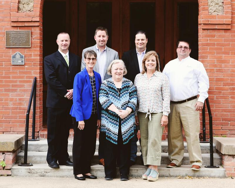 group picture of the Board of Trustees on the steps of the Admin building
