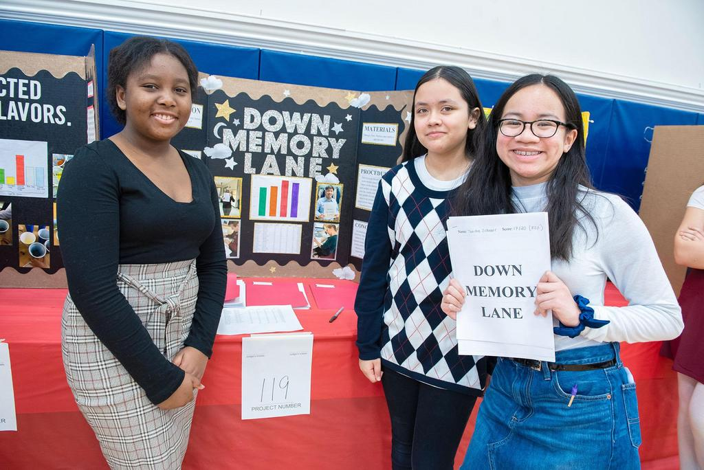 Three students stand in front of their project called Down Memory Lane