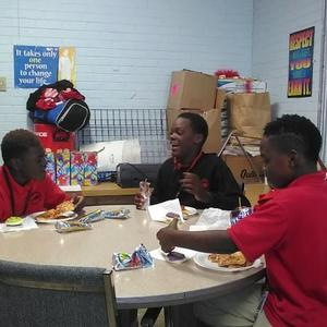 Photo of group of Baker Middle School Students experiencing pizza party reward for good behavior and grades