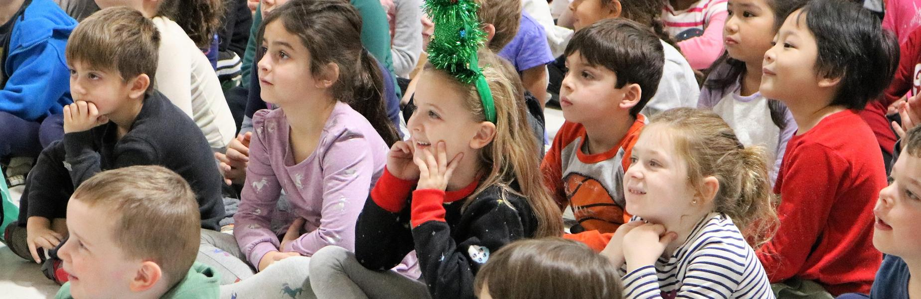 Photo of smiling kindergartners enjoying holiday concert.