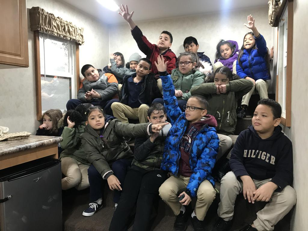 Class seated in the steps of the safety house raising their hands