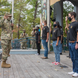 group of students standing before a uniformed officer getting sworn in to the US Army