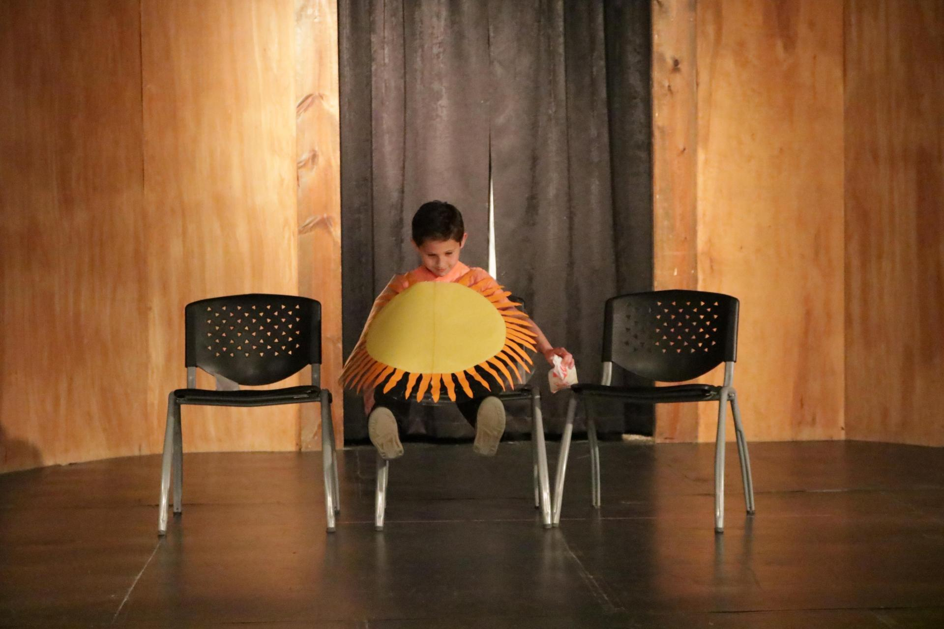 A student plays the sun in a play