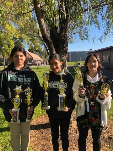 Three female students holding up trophies.