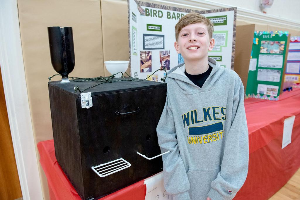A student stands in front of his homemade bird feeder