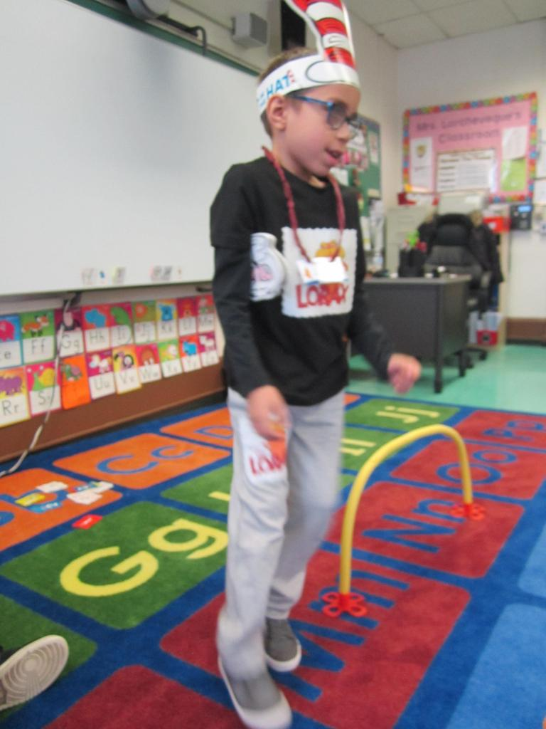 boy wearing a paper cat in the hat hat and a black lorax t-shirt on standing on the class rug