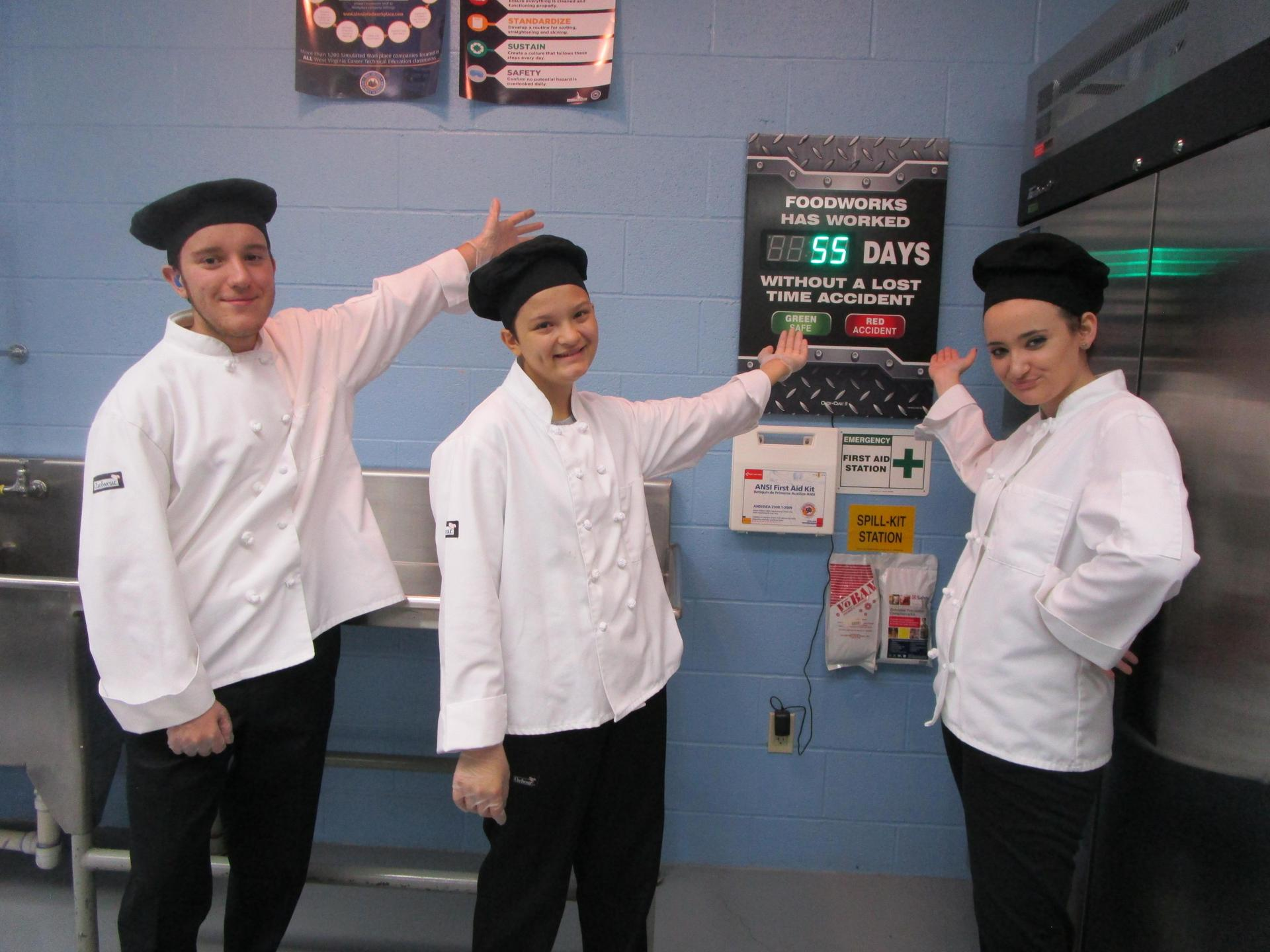 Three ProStart Students pointing toward Accident Free calendar