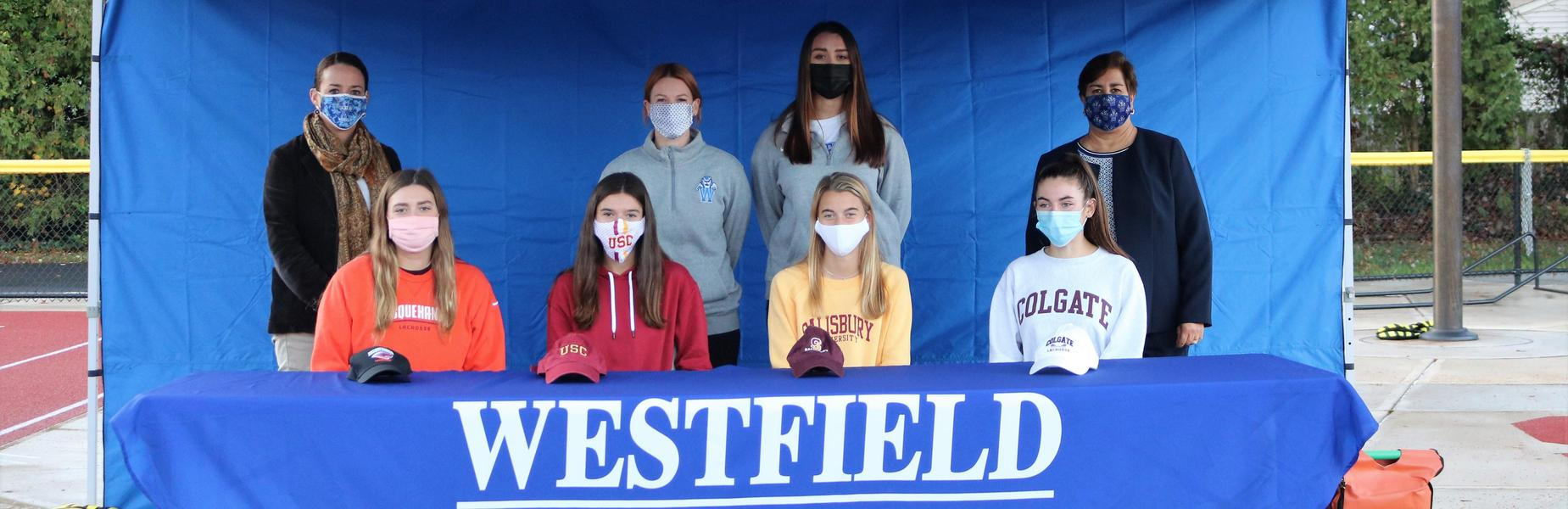FR/LR:  WHS seniors Chloe Pappalardo, Mia Fleming, Brooke Scheuermann, and LJ Kehler signed National Letters of Intent to play lacrosse at colleges/universities next fall.   BR/LR:  WHS Principal Mary Asfendis, Coaches Katie DaSilva and Abigail Cohn, Supervisor of Athletics Sandra Mamary