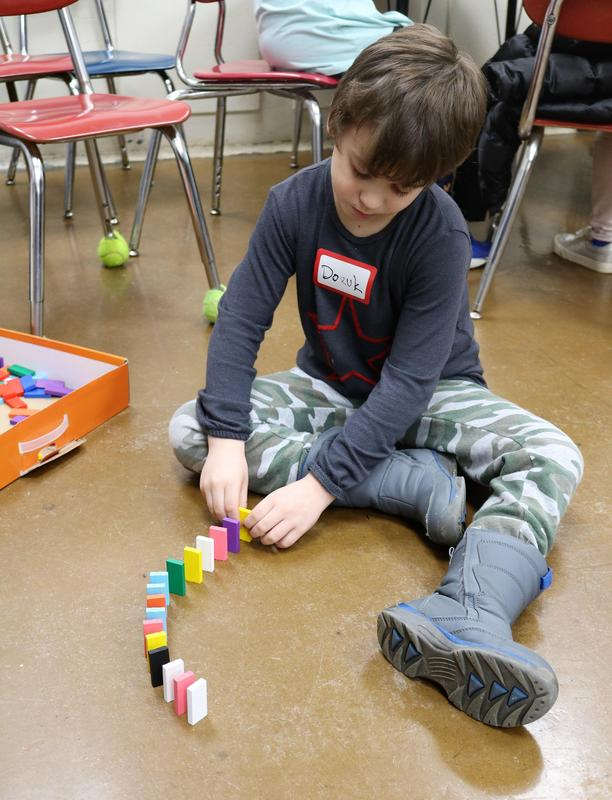 A student tries his hand at building a domino chain reaction during McKinley School's 6th Annual STEAM Night on Jan. 24.