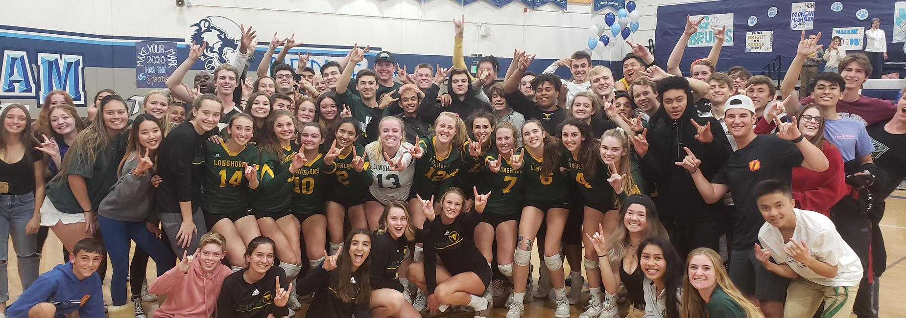 Volleyball team and fans pose after a game