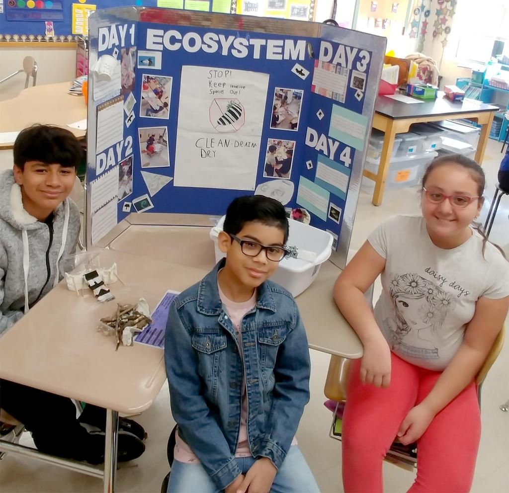 Three Keverian fifth graders display the public service announcement they created for a project entitled 'The Mystery of Loon Lake'