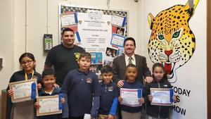 Principal Celebrano, Mr. Petric, and several of the UC science fair winners holding their certificates proudly
