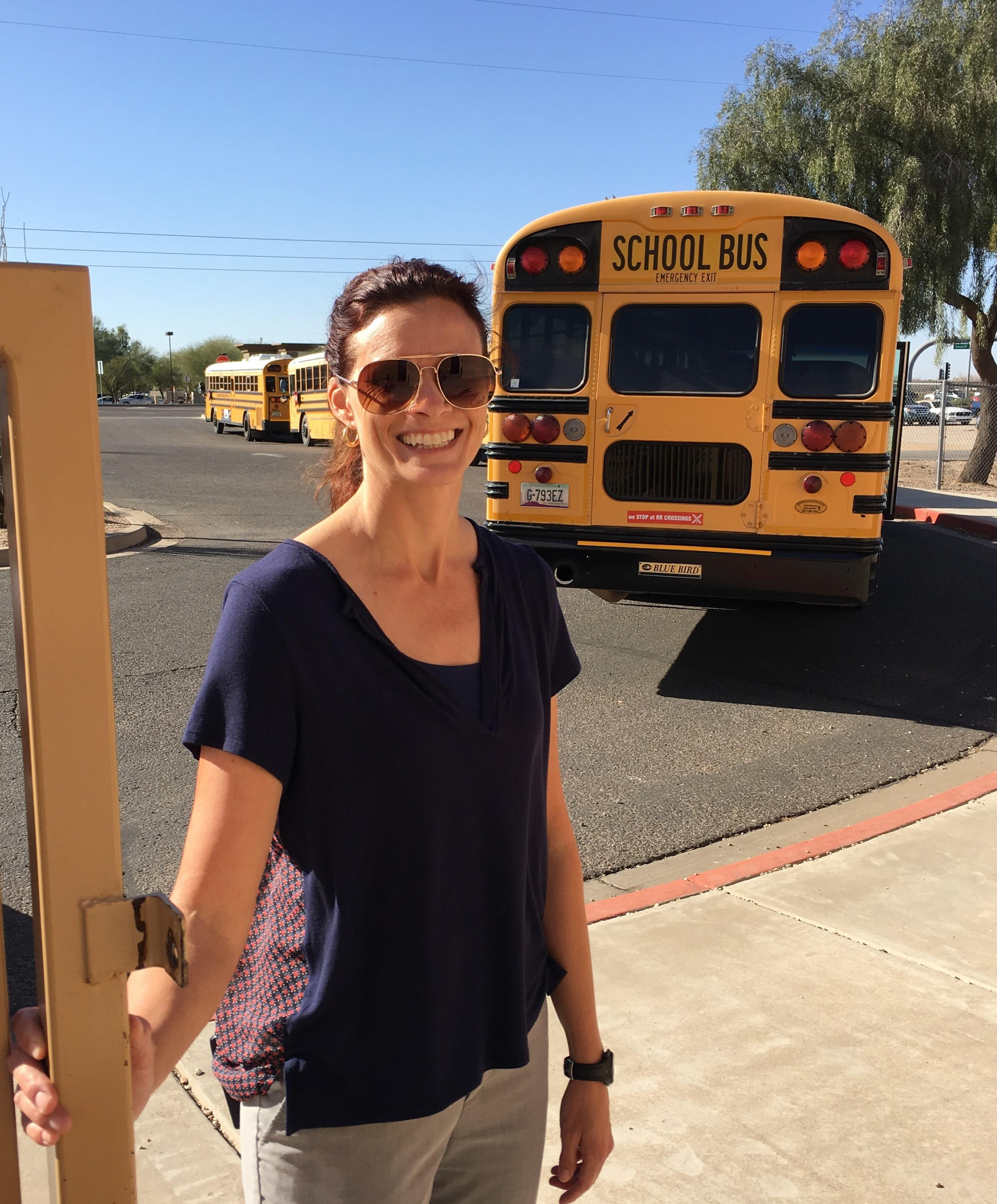 Counselor greeting students by the school bus