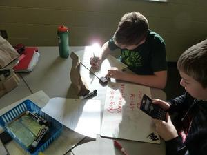 Students work on their equations to solve the problem.
