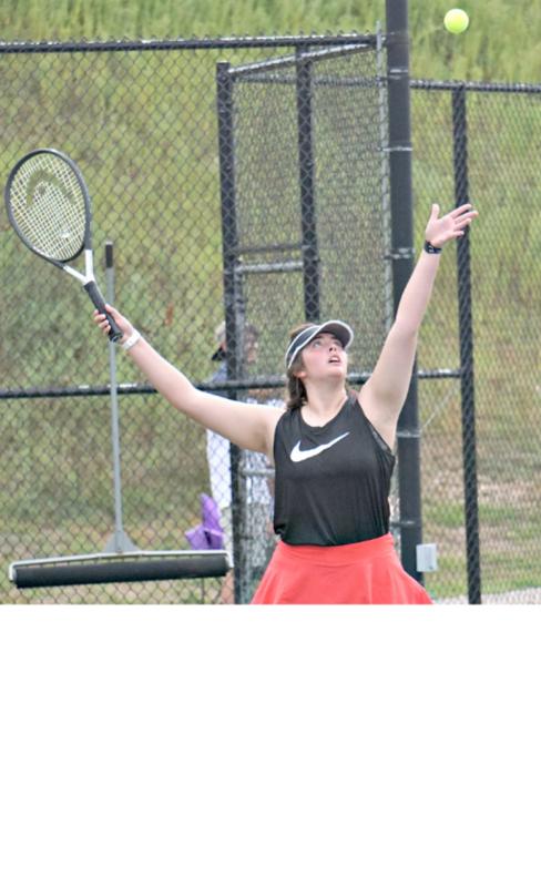 Sophia Brown serves tennis ball
