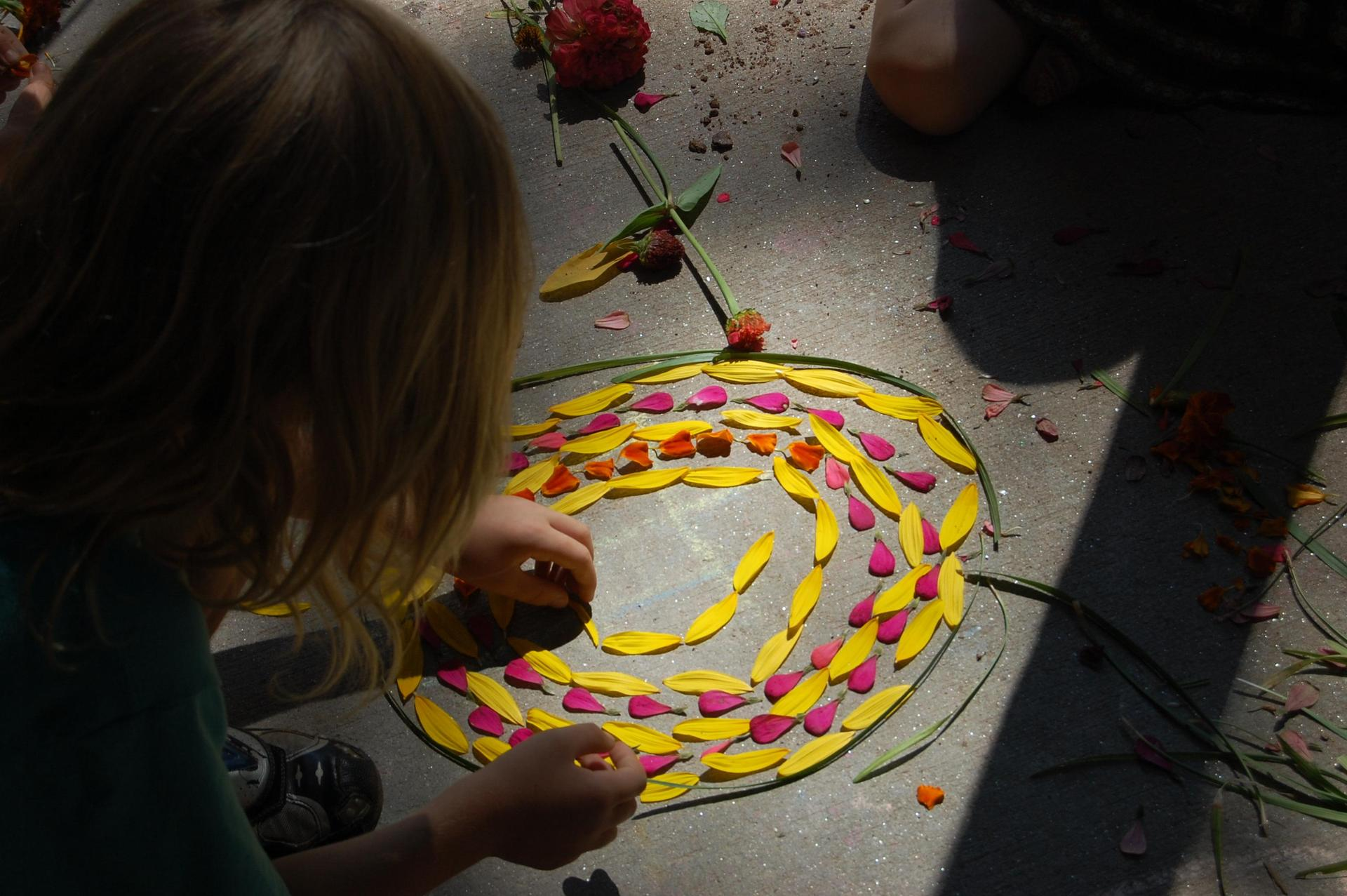 child arranging flower petals in a spiral