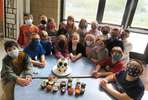 A Lee Elementary 3rd grade class poses with their cake and cupcakes.
