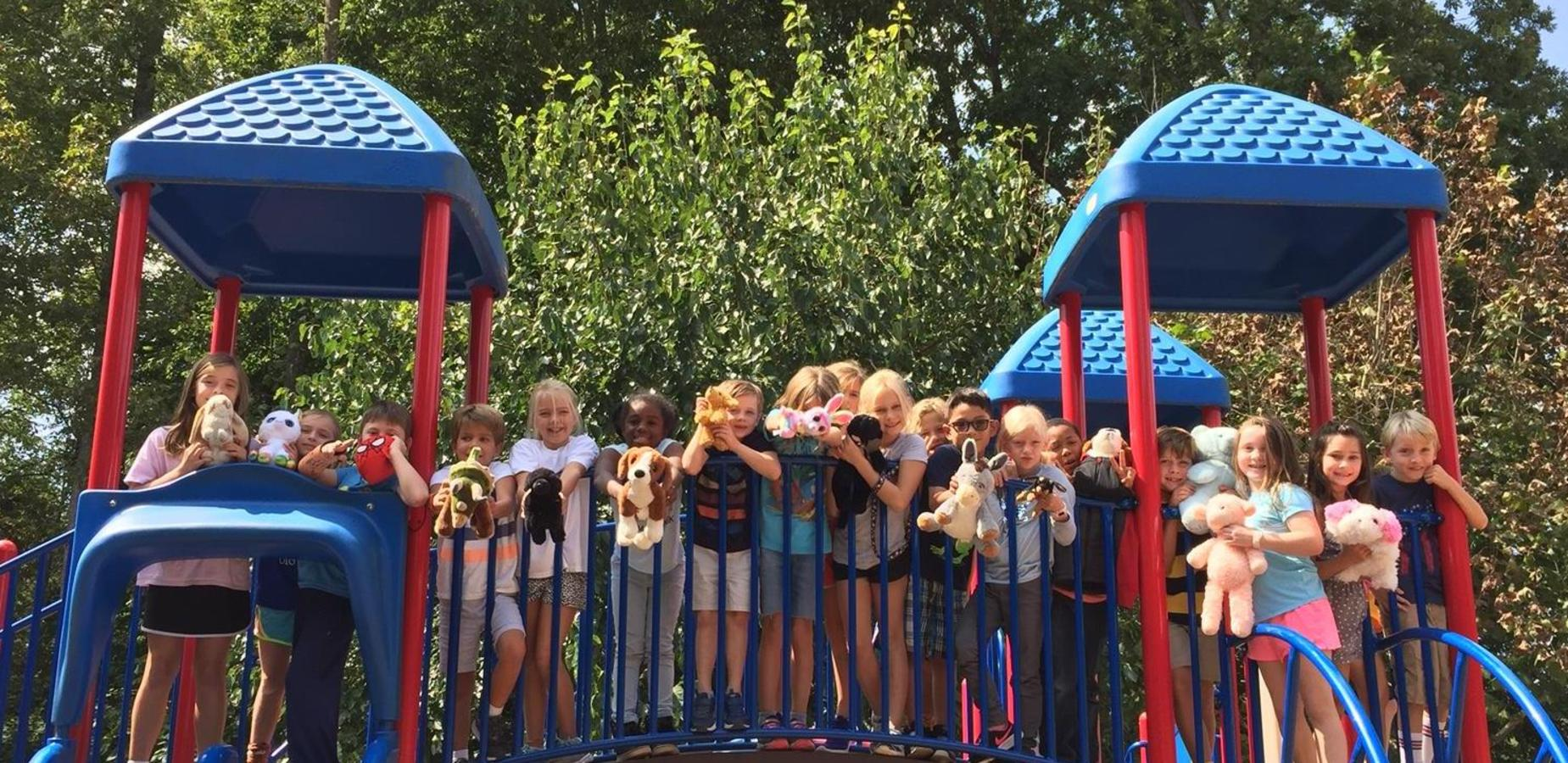 Students holding stuffed animals on the playground