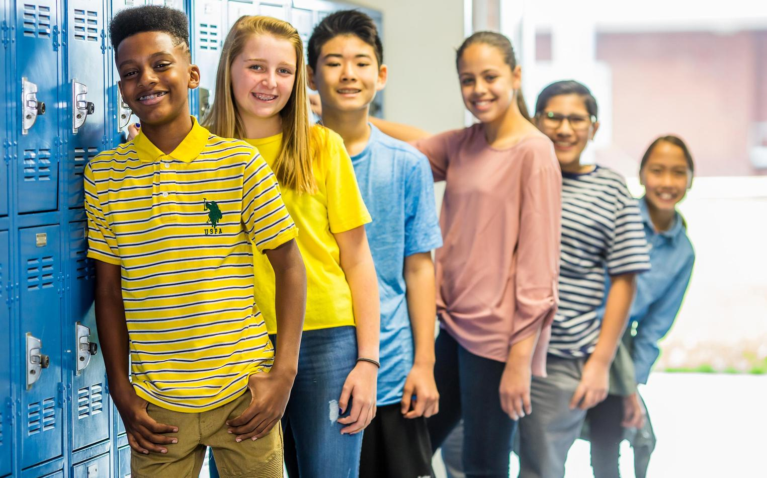 Middle school students posing in a group near their lockers.