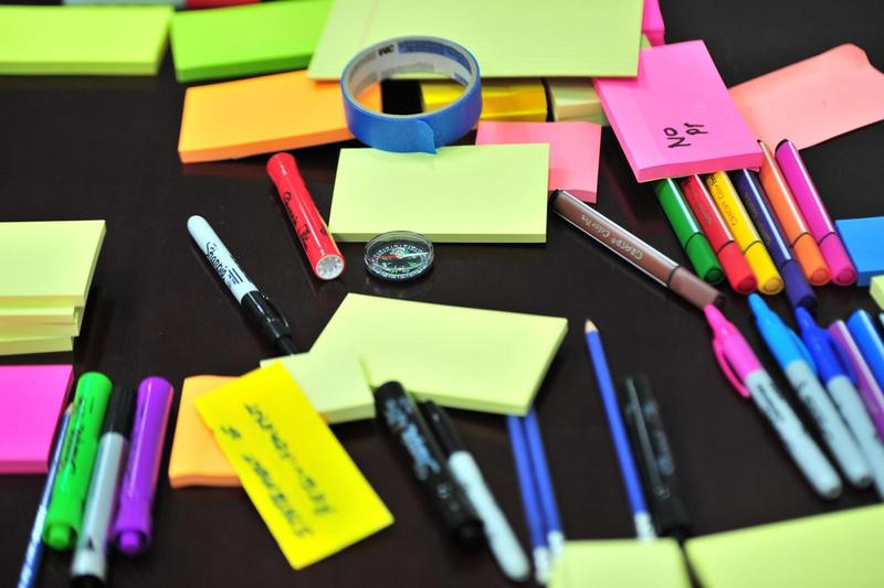 Picture of school supplies - sticky notes, pencils, pens, highlighters.