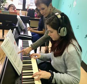 Dr. Elisa Moskovitz working with music student, Scarlett Baker, in the piano lab.
