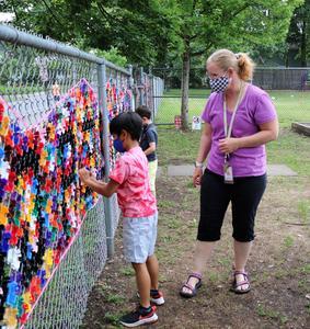 Lincoln student works on playground mosaic as art teacher Amy Hynes looks on.