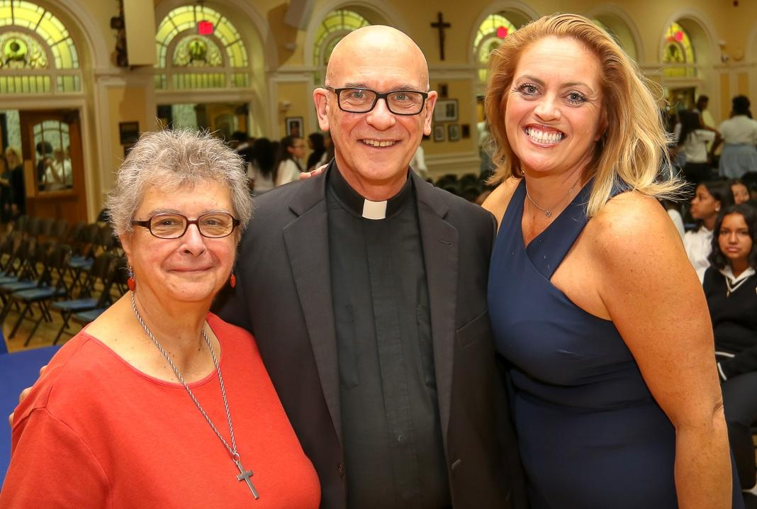 a woman with grey hair and glasses a man in a priests collar and a woman in navy blue stand together smiling