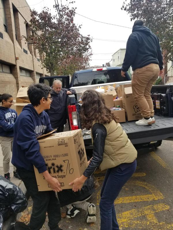 kids lifting boxes of canned good onto Mr. Introna's truck