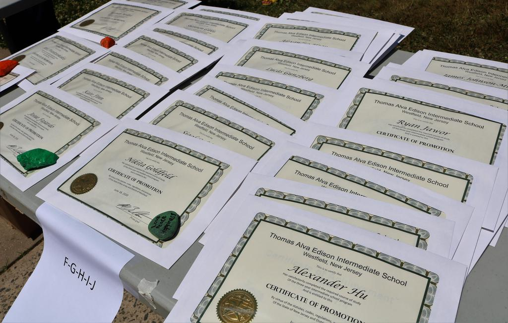 Photo of 8th grade promotion certificates on table.