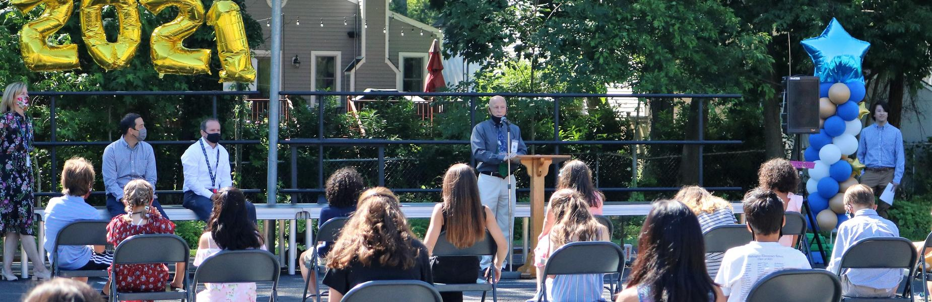 Photo of Washington principal Dr. Andrew Perry addressing 5th graders and their families during awards ceremony.