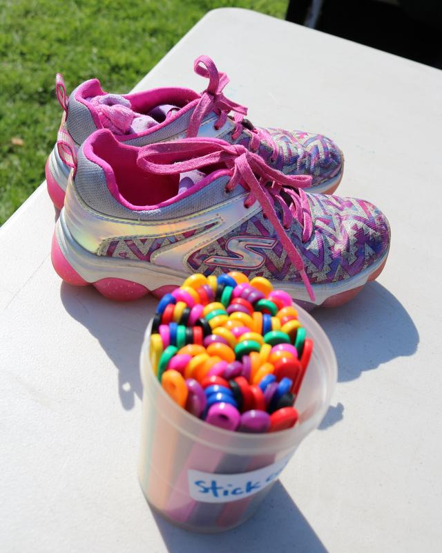 picture of a running sneaker next to the plastic charms given to runners in the Tamaques Mileage Club.