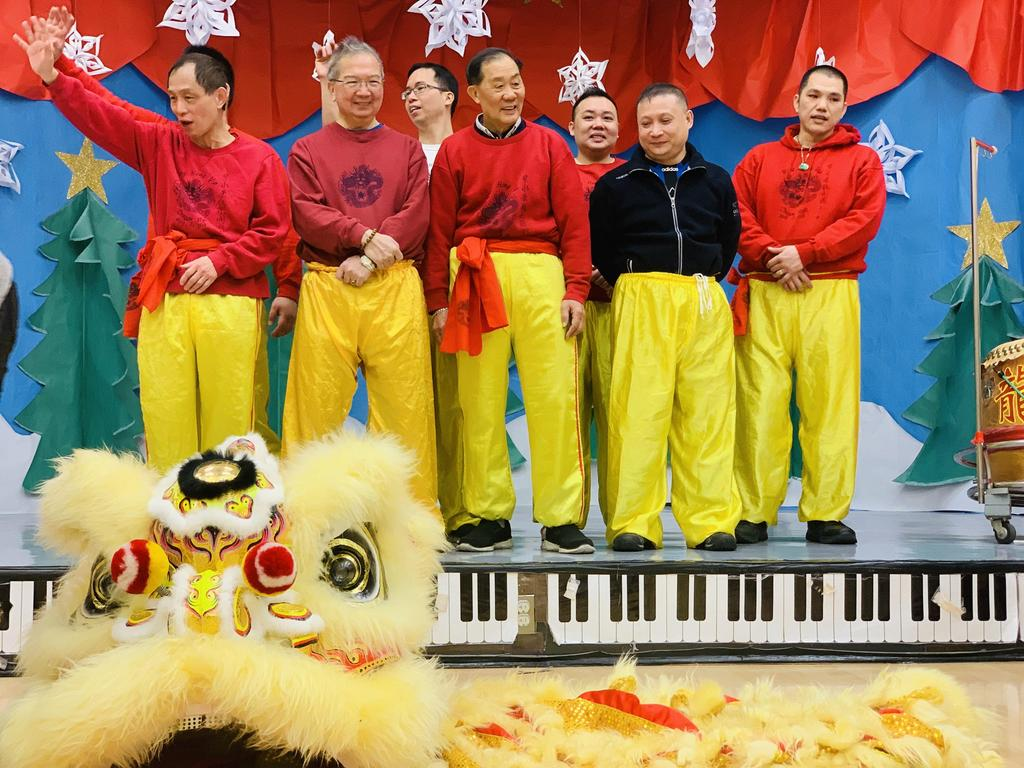 7 Chinese men standing on stage after performing