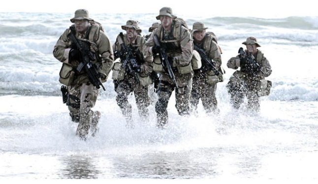 Special forces soldiers running on a beach