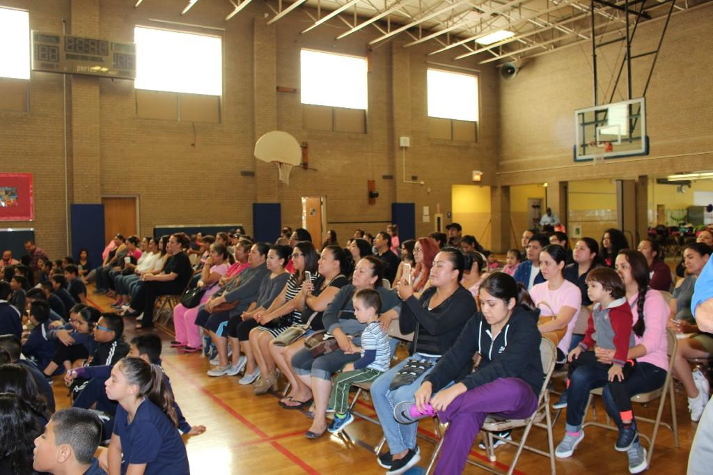 Families seated in chairs during community circle