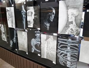 TKHS student artwork is displayed in the art room window along Main Street in the school.