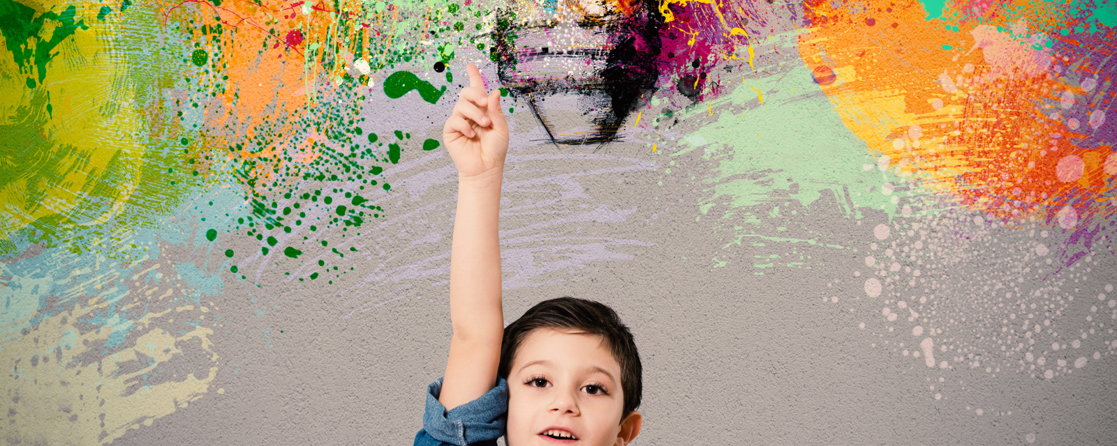 young boy pointing to colorful explosion above him