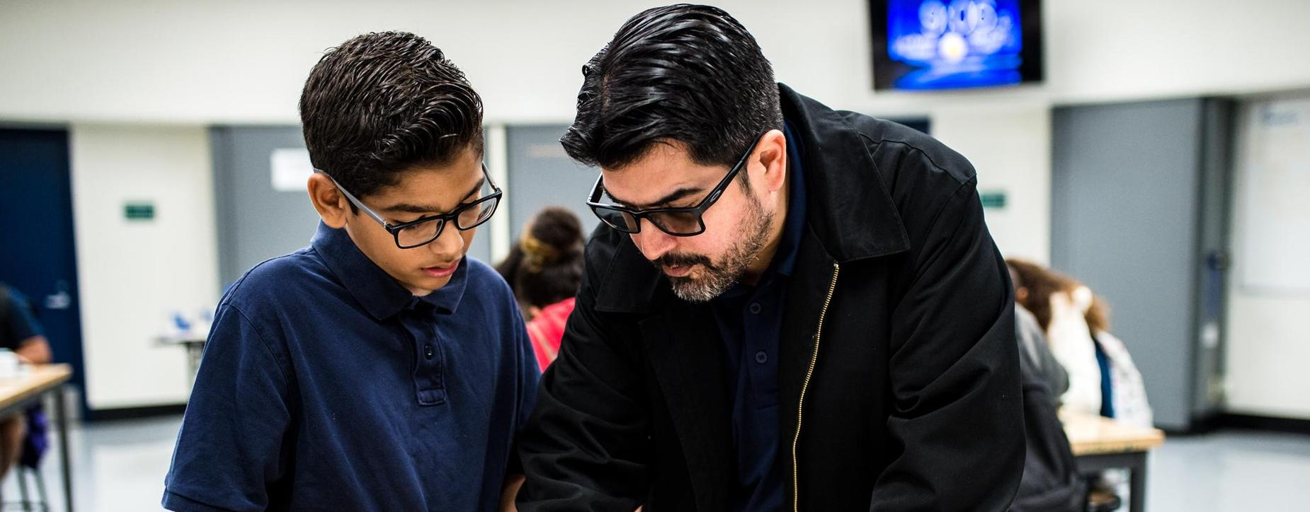 Mr. Avila helping out a student in STEM class