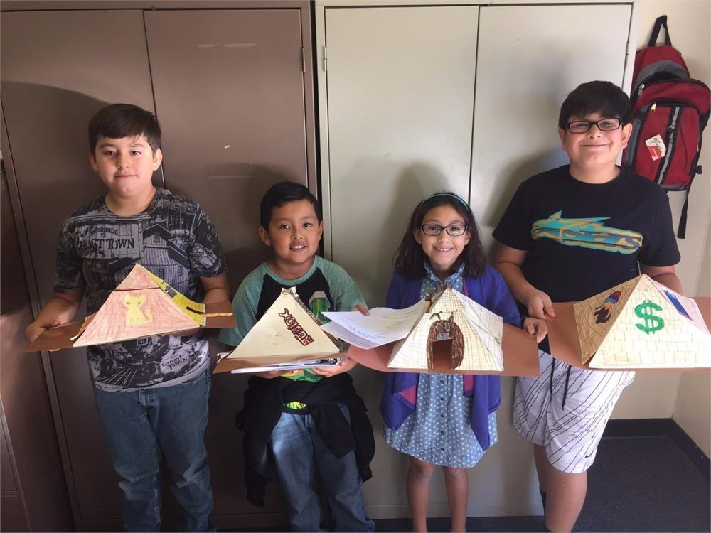 four students with pyramid projects
