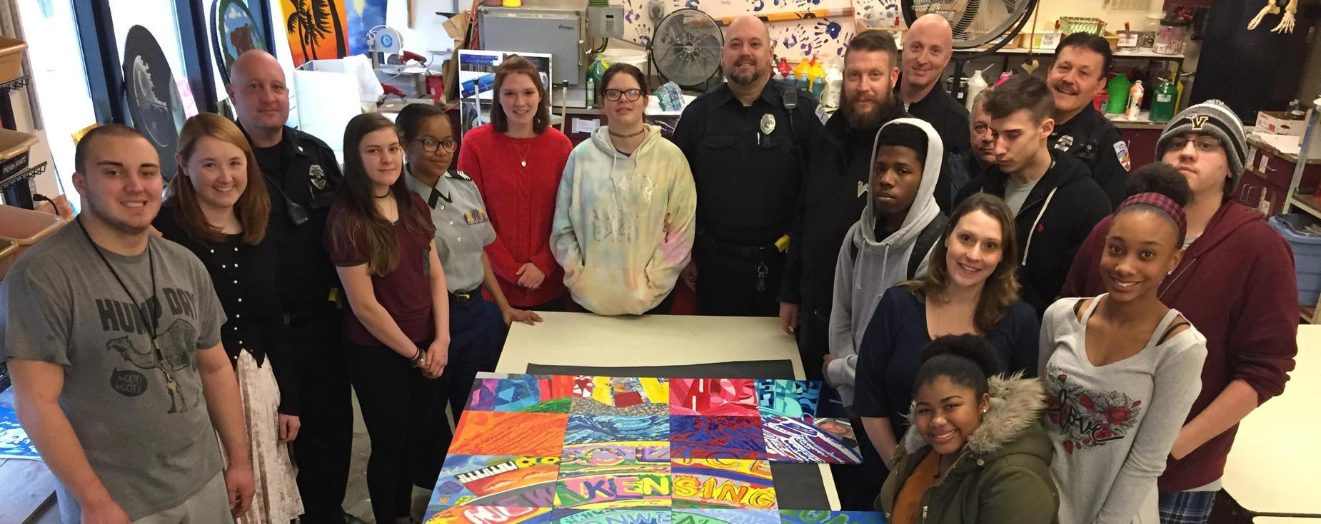 Group photo of the artists that created the Brian Shaw mural and members of the Arnold Police.