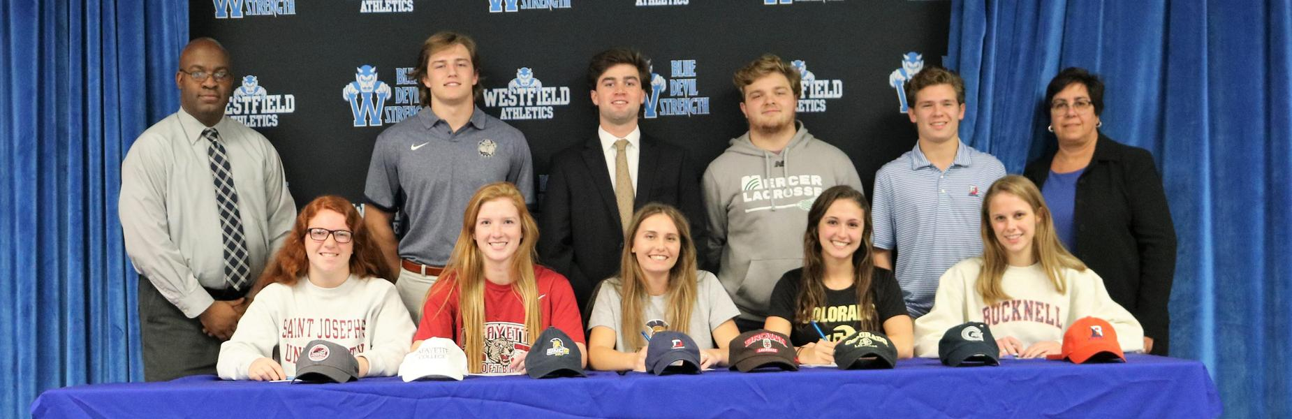:  Nine WHS seniors sign Letters of Intent to play sports at the college level. Seated L-R: Erica Lawrence, Julia Romano, Anna Bowman, Carley Farella, Olivia Shields.  Standing L-R:  WHS Principal Dr. Derrick Nelson, Griffin Aslanian, Devon McLane, Koury Kania, Henry Schwartz, WHS Supervisor of Athletics Sandra Mamary