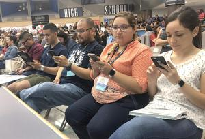Edinburg CISD teachers use their cell phones to discover blended learning software applications during the 8th Annual Innovate Conference at Vela High School.