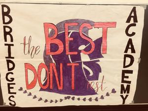 Paper five foot square sign hung in the gym that reads the best don't rest