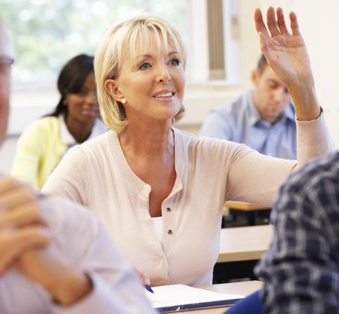 Senior female student in class raising hand