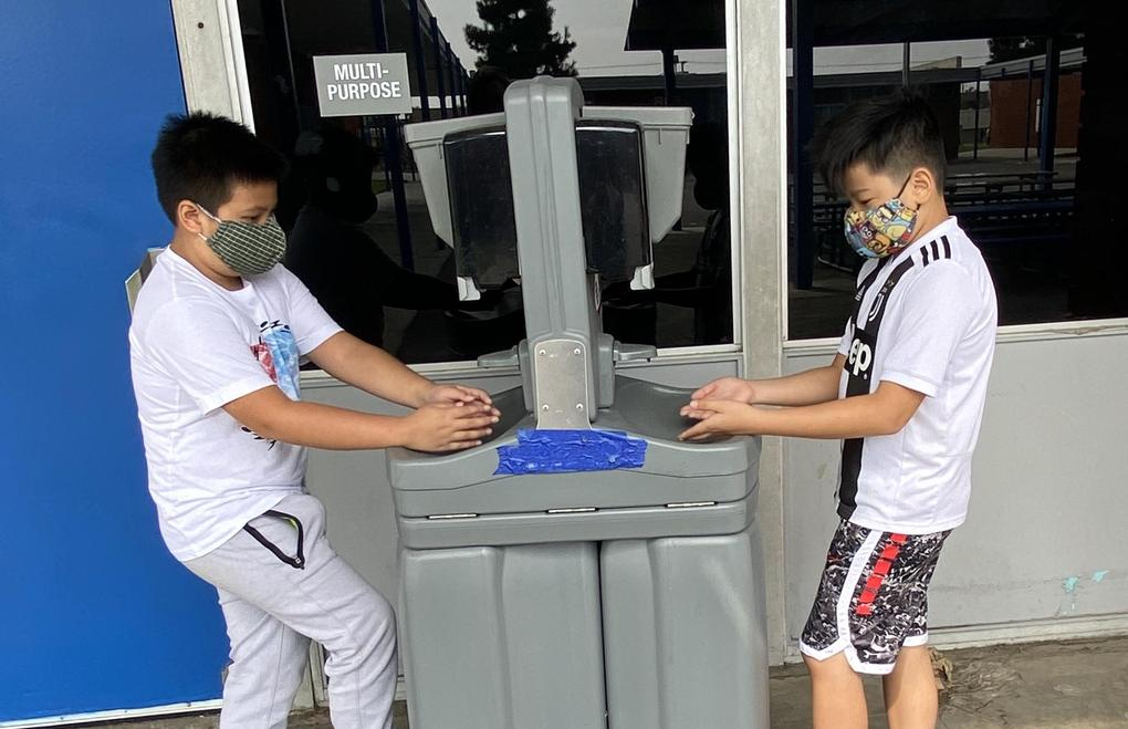 Students use a handwashing station.