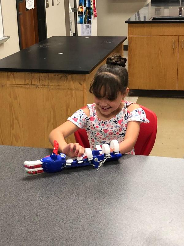 an elementary student trying on a prosthetic arm