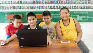 four elementary aged boys using a computer together in a classroom