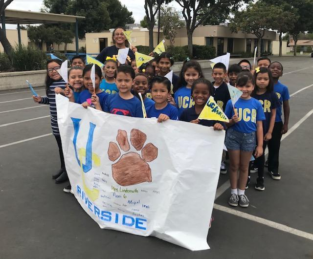 Students at Sunnymeadows Elementary School wear UCR t-shirts, hold a UCR banner and hold UCR pennants to celebrate College Kick Off Day