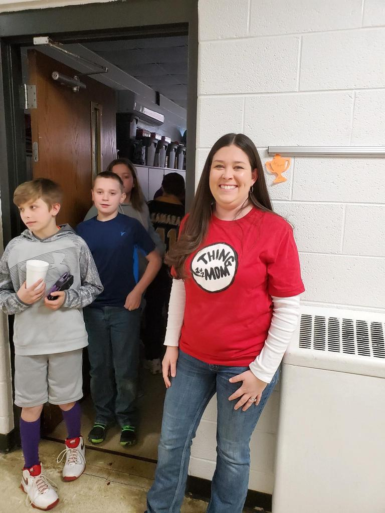 Mrs. Haynes wearing Thing Mom shirt with students lined up