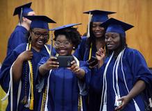 4 female graduates in their bright blue cap and gowns taking a selfie with one of the girls cell phone and smiling.