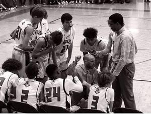 a picture of the boys basketball team on the sideline with coach